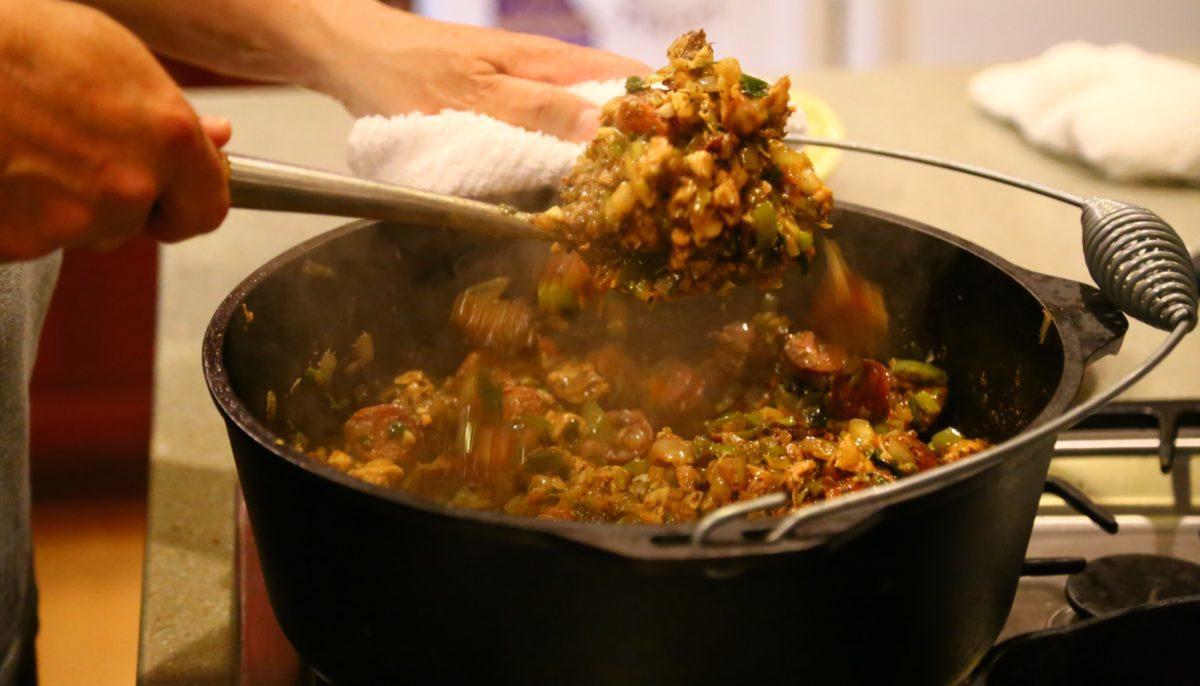 cajun jambalaya being stirred in a Dutch oven