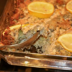 Stuffed Artichoke Casserole with lemon slices being spooned out of casserole
