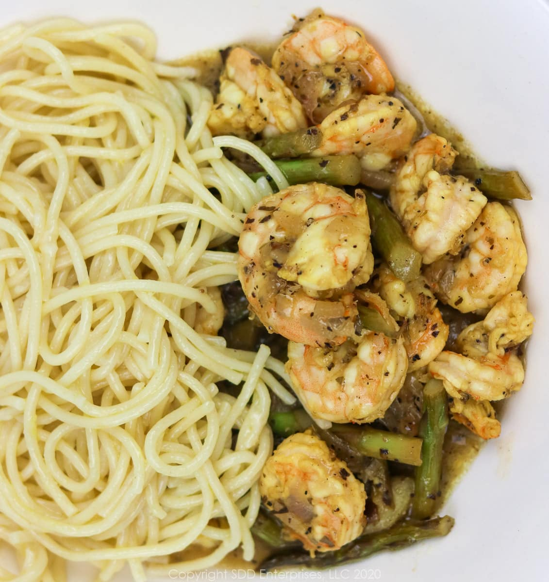 sauteed shrimp and asparagus with pasta in a white bowl