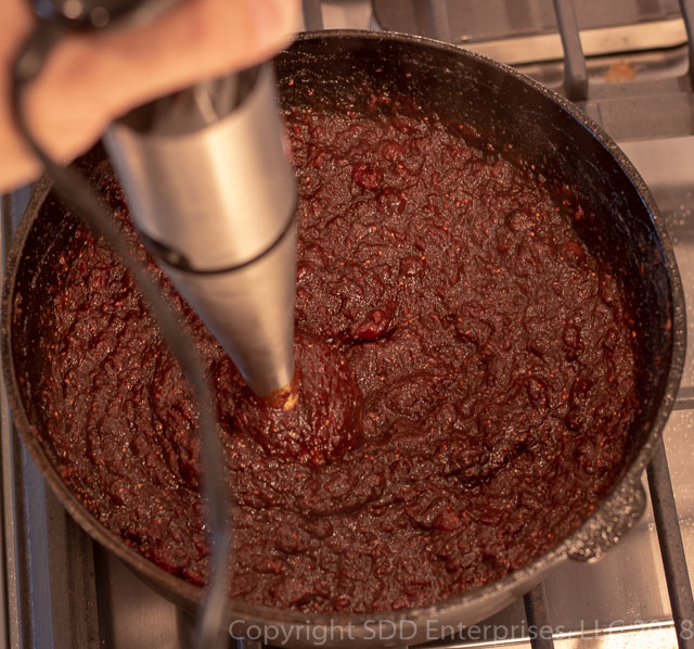 Cranberry BBQ Sauce in the dutch oven with immersion blender