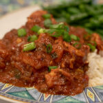 Shrimp Creole on a plate with green onions and green beans