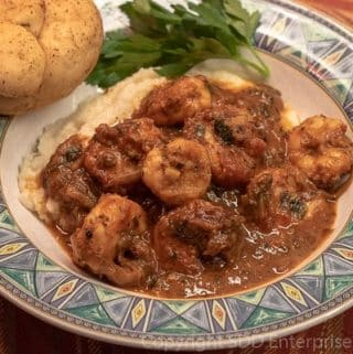 Shrimp and Grits in a green bowl with roll and parsley
