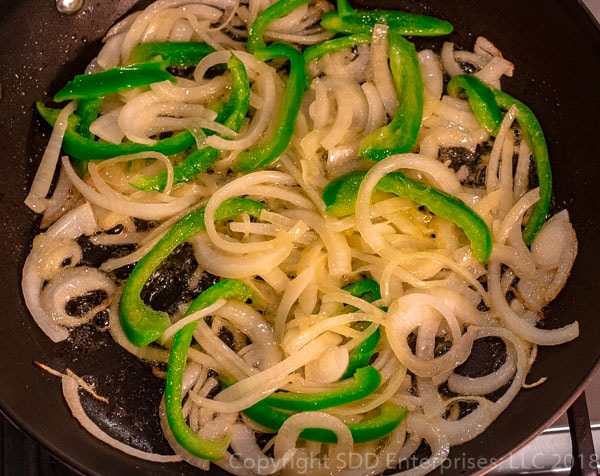 sliced onions and peppers sauteing in butter