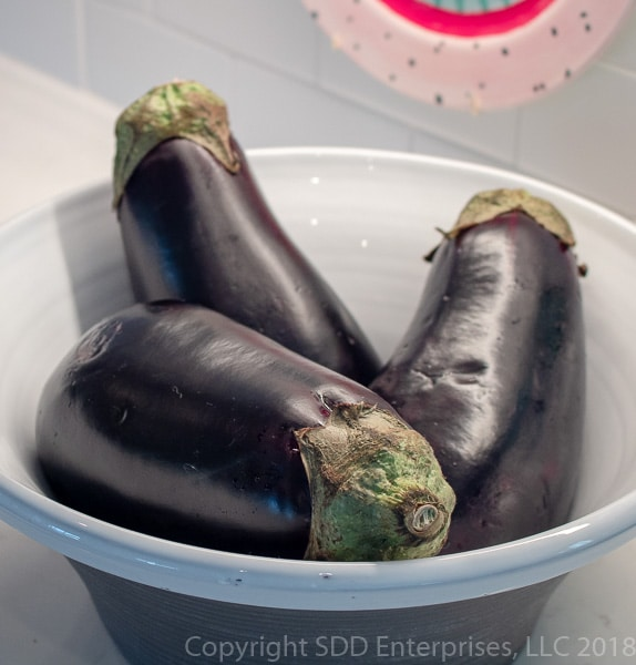 Three eggplant in a bowl