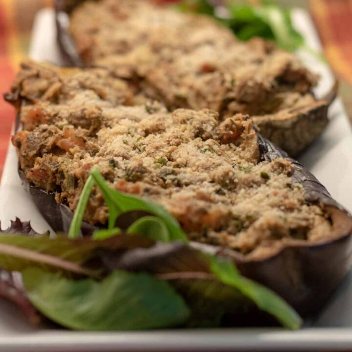 Roasted eggplant stuffed with shrimp and vegetables on a platter with garnishment