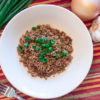 cajun dirty rice in a white bowl with green onions, yellow onion, garlic and fork