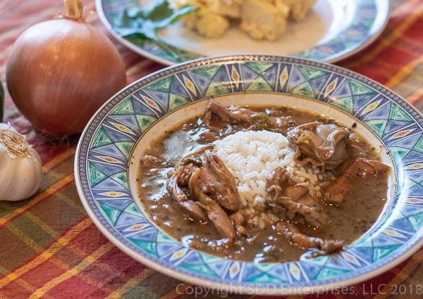 Turkey Oyster Gumbo in a bowl with rice, spoon and potato salad