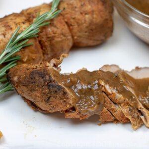 Sliced pork tenderloin with meyer lemon sauce and sprig of fresh rosemary