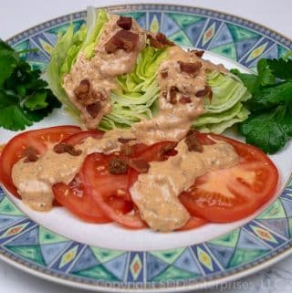 cajun thousand island dressing on tomatoes and lettuce on a plate