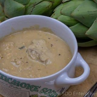 oyster artichoke bisque in a bowl with 2 fresh artichokes
