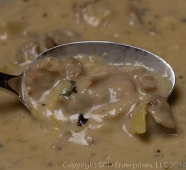spoon full of oysters and artichokes in oyster artichoke bisque