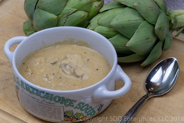 bowl of oyster artichoke bisque with fresh artichokes