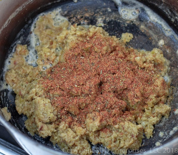 creole seasoning added to purred vegetables in a dutch oven