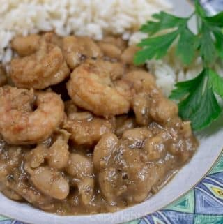 white eans with shrimp in a bowl with rice and parsley garnish
