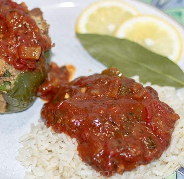 creole sauce served over rice with stuffed pepper and garnished with lemon and bay leaf