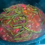 creole green beans smothering in cast iron dutch oven