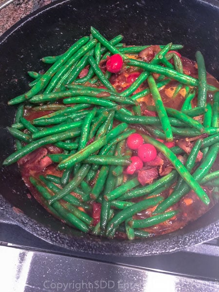 tomatoes added to the green beans in a dutch oven