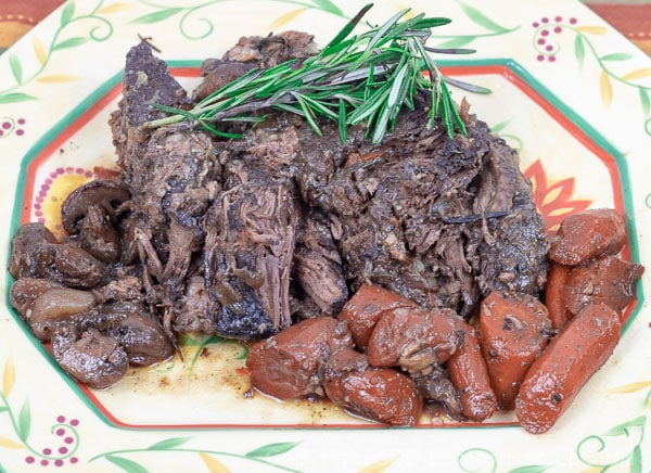 tender pot roast on a platter with carrots, mushrooms and rosemary