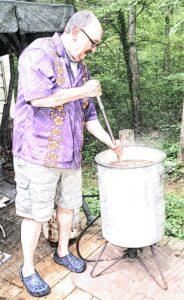 man stirring crawfish boil pot