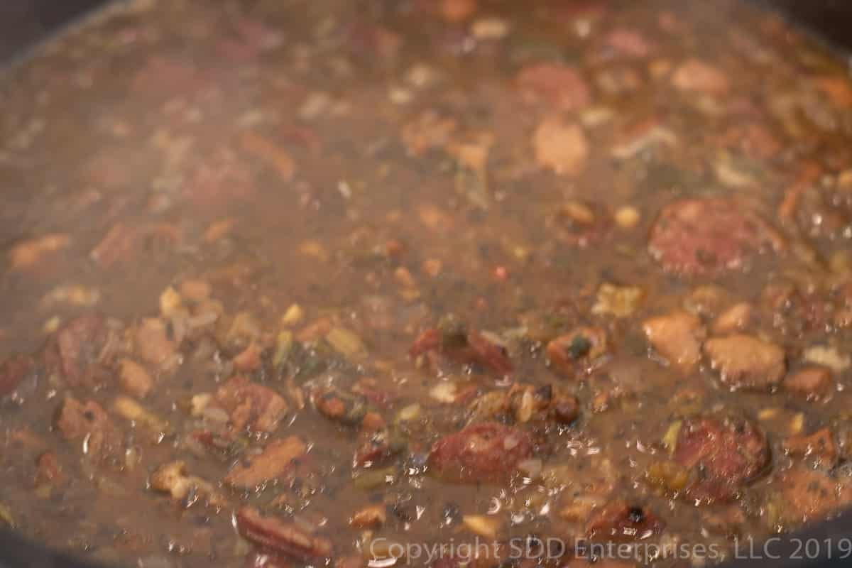 rice added to stock in a dutch oven for cajun jambalaya