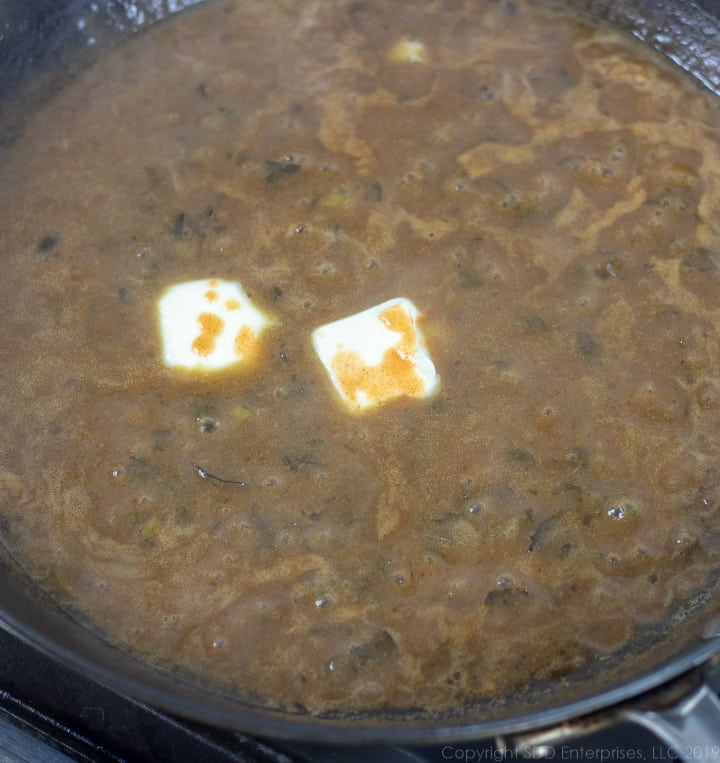 finishing the meuniere sauce with some butter and Tabasco sauce in a cast iron pan