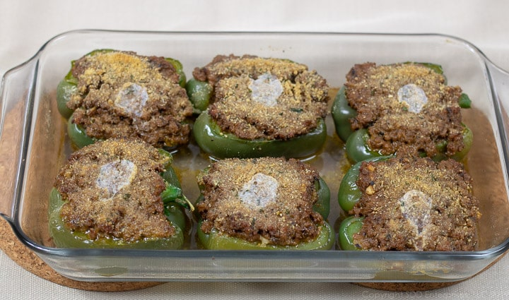 stuffed ell peppers in a baking dish right out of the oven