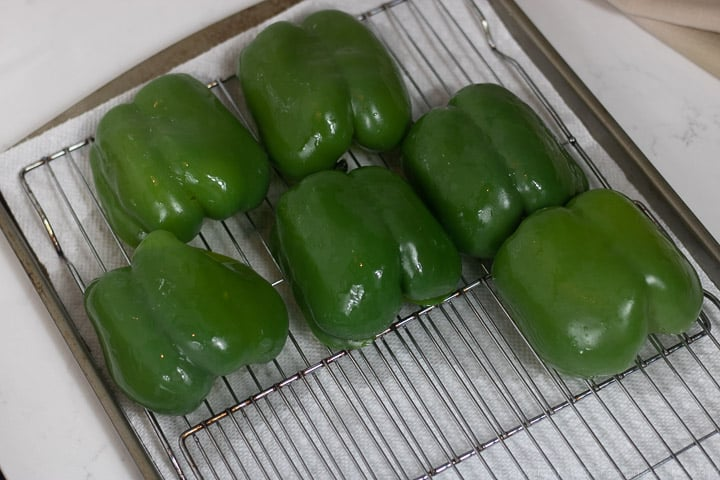 parboiled green bell peppers on a cooling rack
