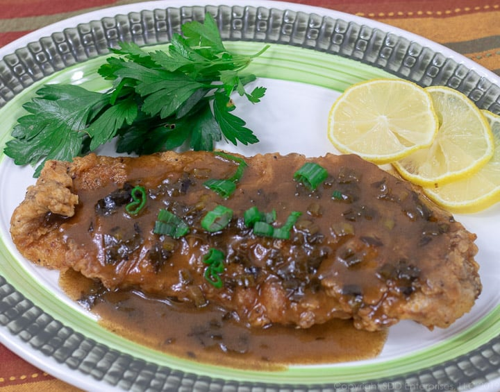 fried trout with meuniere sauce on a green rimmed platter and garnished with parsley and lemon slices