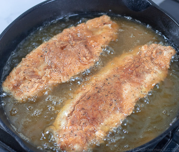 two fish filets frying in a cast iron pan