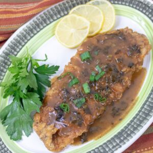 Fried trout with meuniere sauce and garnish on a platter