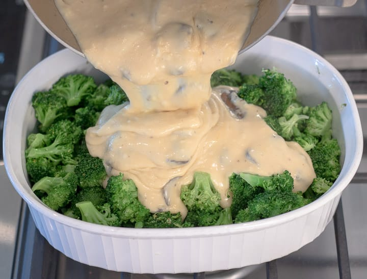 pouring cheesy bechamel sauce into broccoli florets for broccoli casserole