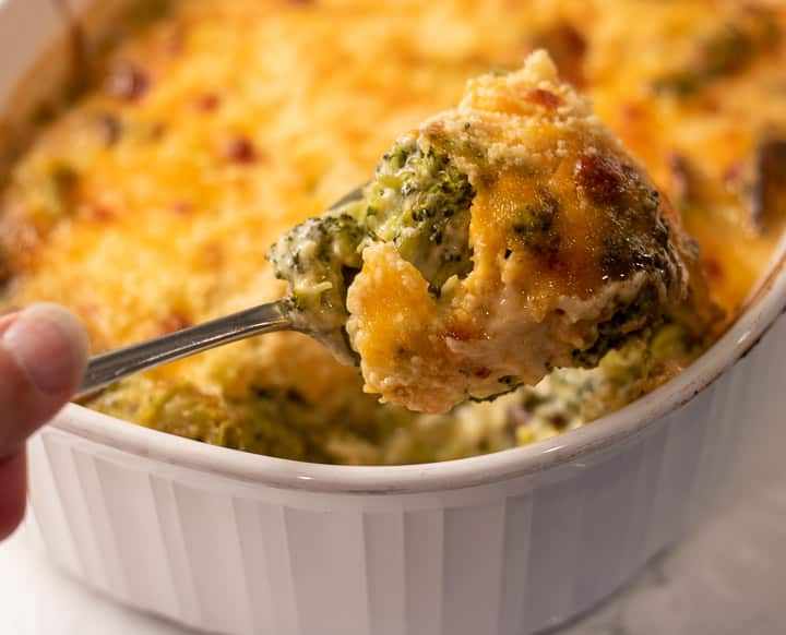 broccoli cheese and mushroom casserole in a white baking dish and a spoon