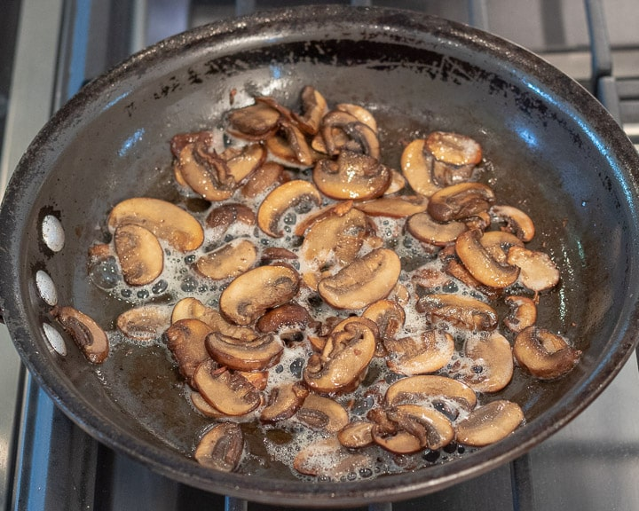mushrooms being sauteed in a saute pan