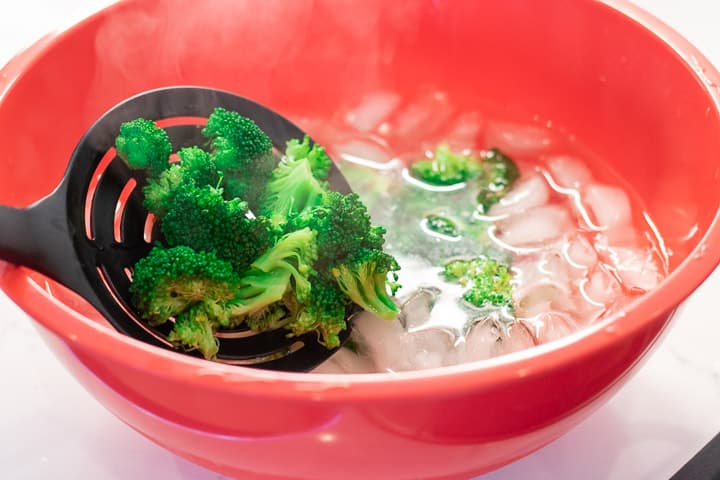 steamed broccoli being placed in an ice bath in a red bowl