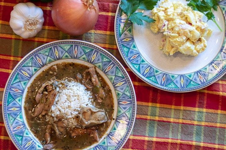 turkey oyster gumbo in a bowl with a plate of potato salad and garnishment