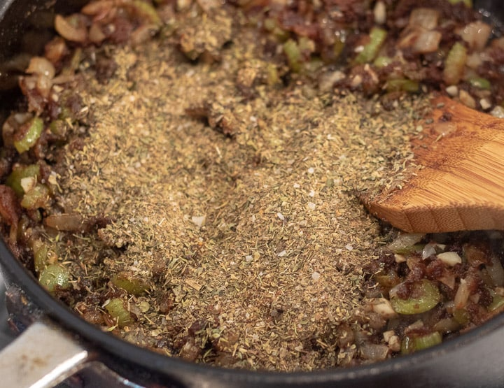 herbs and spices added to trinity in a frying pan for turkey oyster gumbo