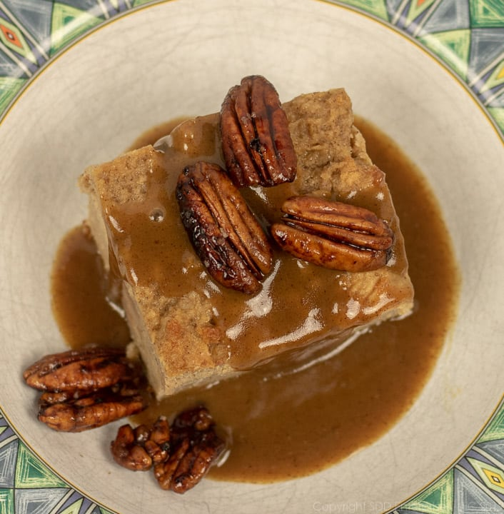 bread pudding with cane syrup sauce topped with pecans in a white bowl with green trim