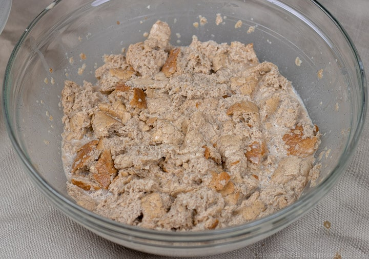 bread pieces soaking in custard in a clear glass bowl for bread pudding