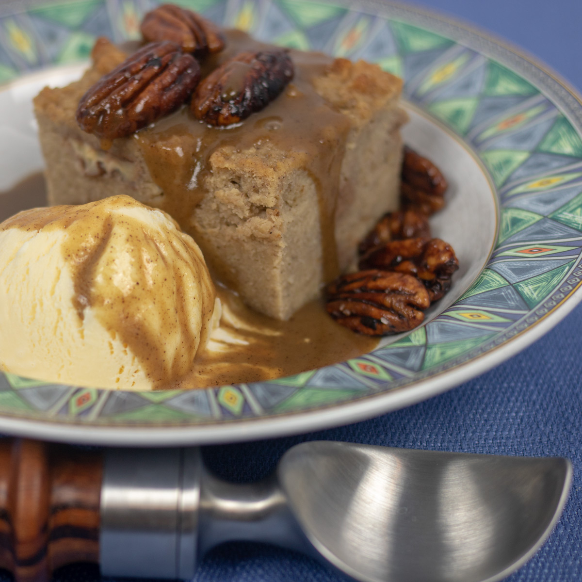 bread pudding with cane syrup rum sauce and glazed pecans with a scoop of vanilla ice cream in a bowl with green trim and an ice cream scooper