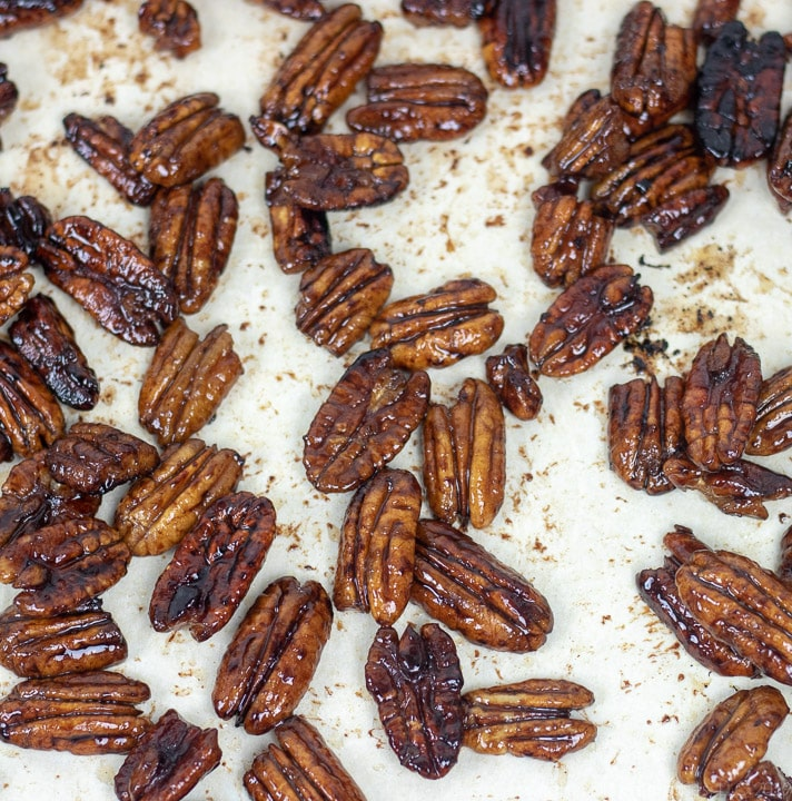 glazed pecans cooling on parchment paper
