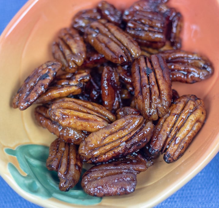 glazed pecans with rum and cane syrup in a small orange and green bowl