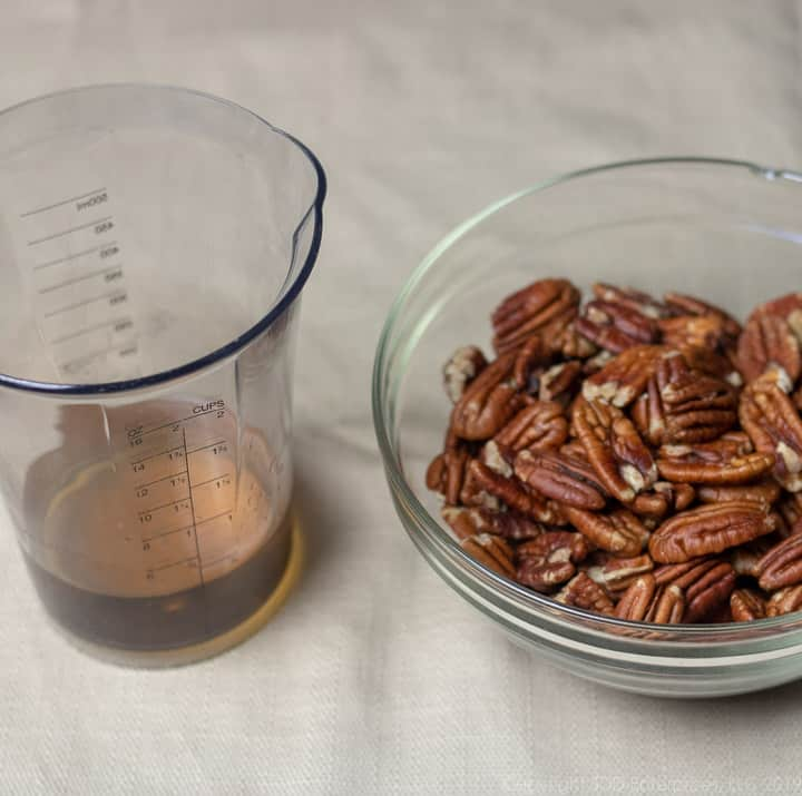 pecan halves in a bowl with a measure of dark rum