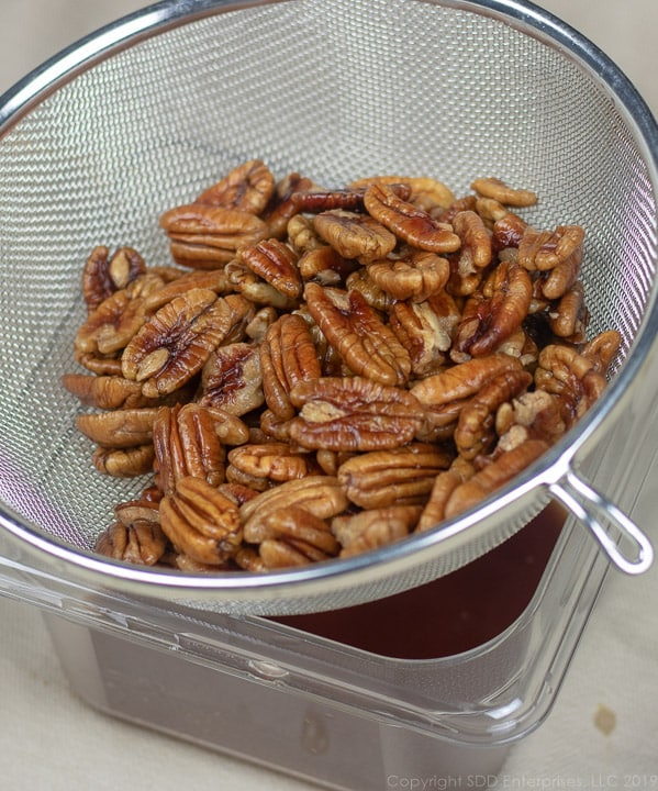 pecans marinated in rum being strained into a container