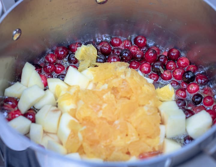 orange pulp and apples added to a sauce pan with cranberries and orange juice for cranberry relsih