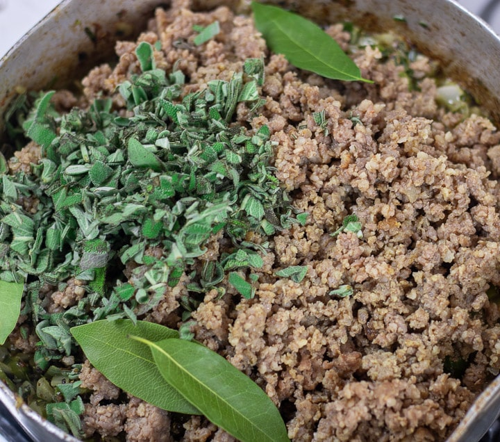 sausage, bay leaves and sage added to onions in a frying pan for oyster dressing