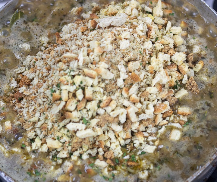 stale bread added to dressing mix in a frying pan for oyster dressing