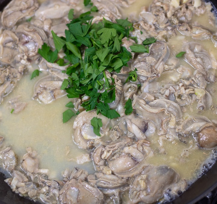 oysters with parsley sauteing in a skillet for oyster dressing