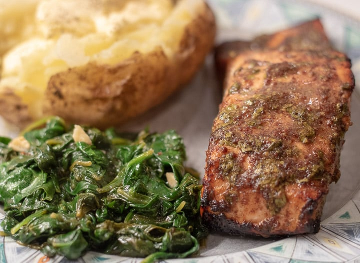 grilled marinated salmon with creamed spinach and a buttered baked potato on a plate