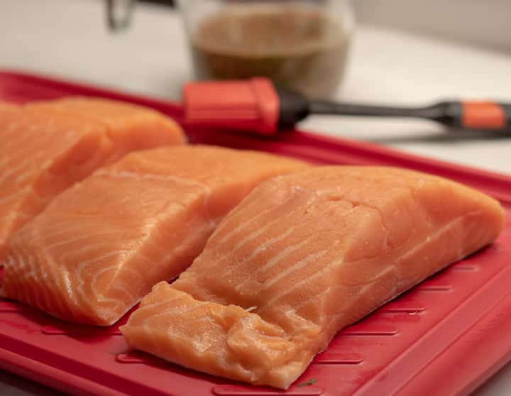 fresh uncooked salmon filets on a red platter with a brush and marinade
