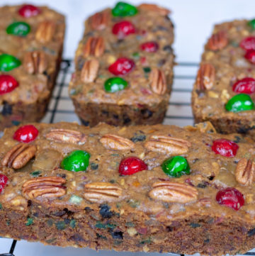 four fruitcakes on a cooling rack